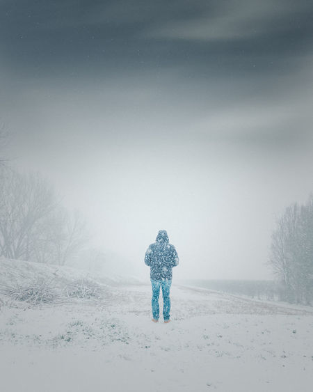 Rear view of man standing on snow covered landscape during snowfall