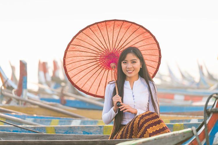 Portrait of smiling young woman holding umbrella standing outdoors