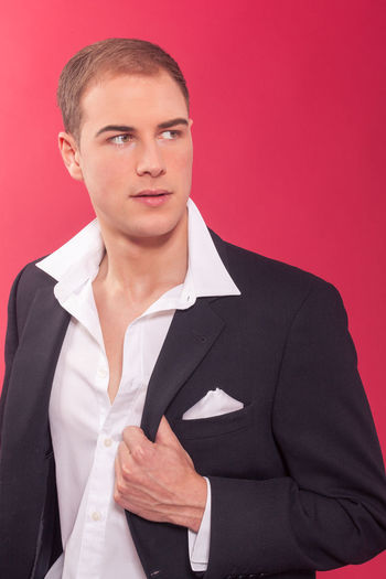 Handsome suave young man holding the lapel of his stylish jacket and looking off to the side on a red background Elegant Pensive Stylish Thinking Business Businessman Confidence  Corporate Business Day Handsome Holding Lapel Looking At Camera Masculine Men One Person People Portrait Real People Serious Studio Shot Suit Thoughtful Well-dressed Young Adult