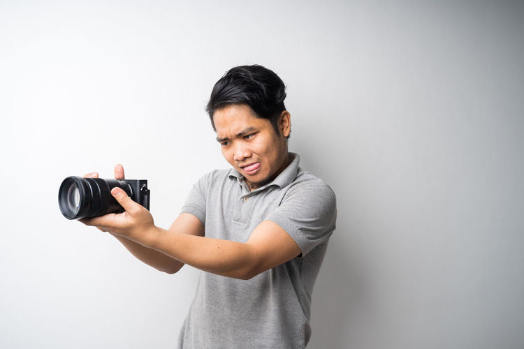Man holding camera while standing against white background