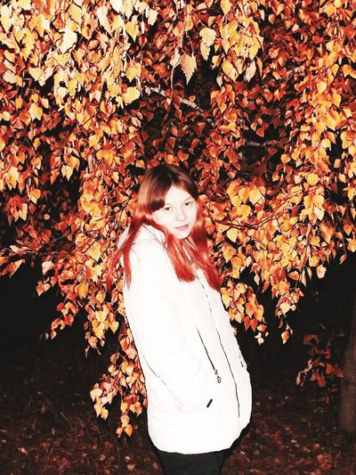 Portrait of woman standing against plant during autumn at night