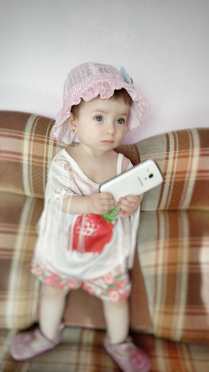 childhood, real people, communication, wireless technology, mobile phone, baby, babyhood, toddler, one person, indoors, technology, cute, portable information device, casual clothing, home interior, holding, lifestyles, full length, looking at camera, standing, day, close-up