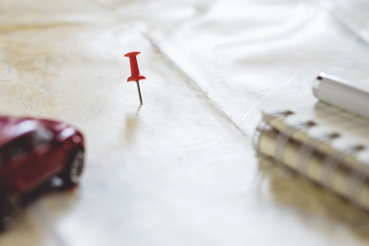 Close up of straight pin with books and toy car on map