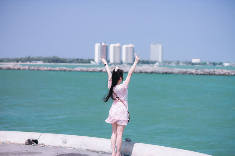 Rear view of woman with arms raised standing against sea in city