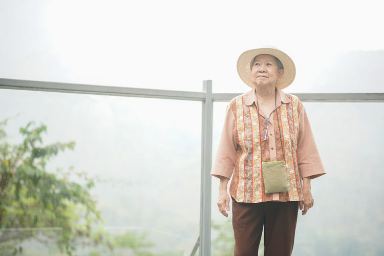Full length of woman wearing hat standing against railing