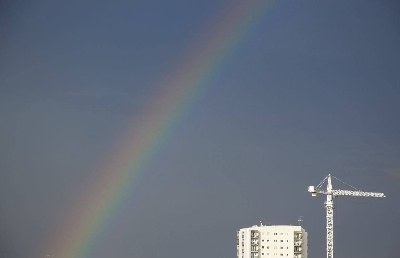 LOW ANGLE VIEW OF RAINBOW OVER CITY AGAINST SKY