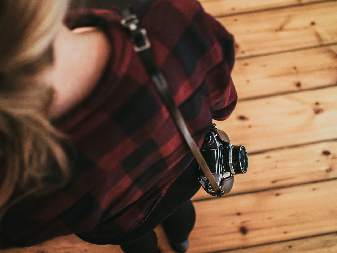 High angle view of woman standing with camera on hardwood floor