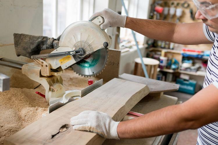 Midsection of carpenter working at workshop