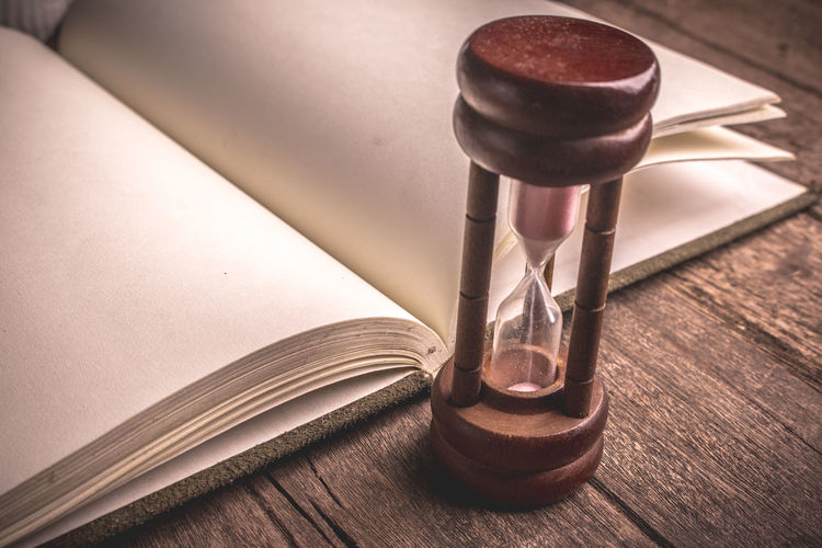 Close-Up Of Hourglass By Open Blank Book On Wooden Table