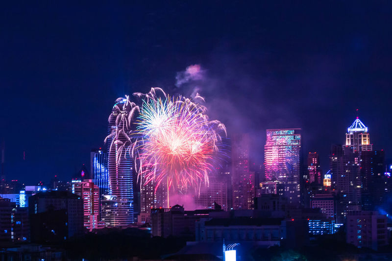 Firework display over illuminated buildings in city at night