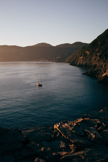 Scenic view of a boat in a sea at sunset, cinque terre, italy.