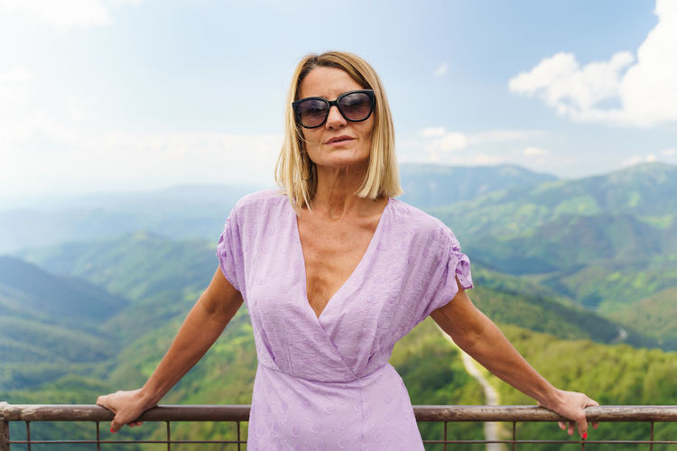 Portrait of woman standing on mountain against sky
