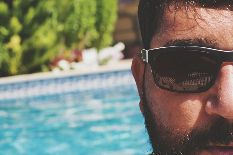 Cropped image of man wearing black sunglasses against swimming pool on sunny day