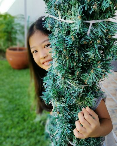 Close-up portrait of girl holding plant in yard
