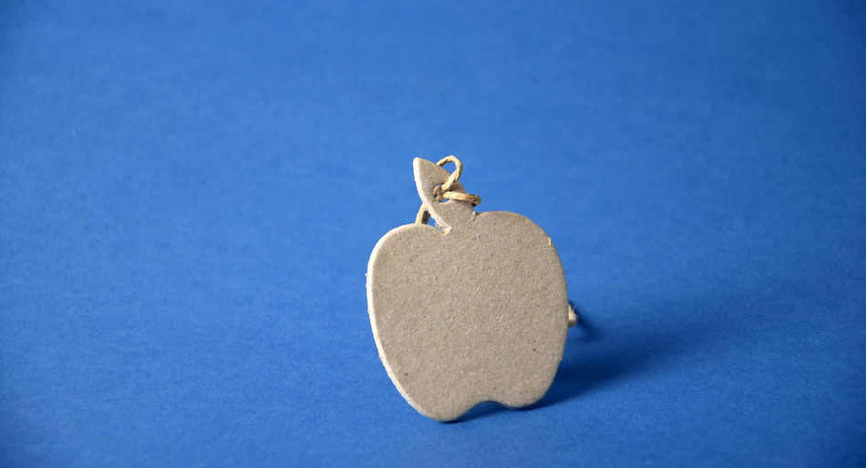 Close-Up Of Apple Shaped Cardboard On Blue Table