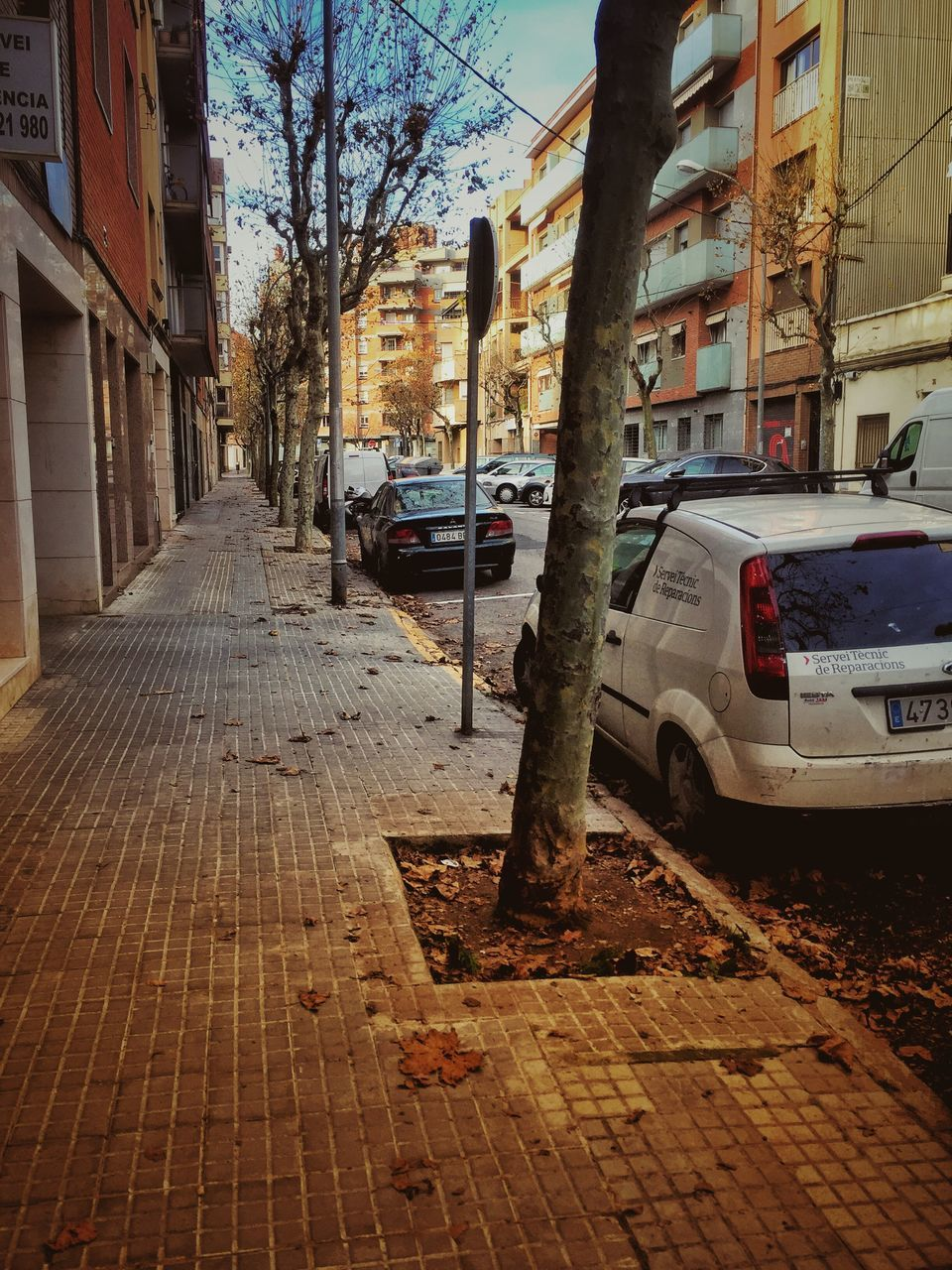 city, architecture, car, street, motor vehicle, mode of transportation, building exterior, built structure, transportation, building, land vehicle, footpath, tree, sidewalk, direction, residential district, no people, outdoors, day, nature, place, neighborhood, paving stone, location, alley