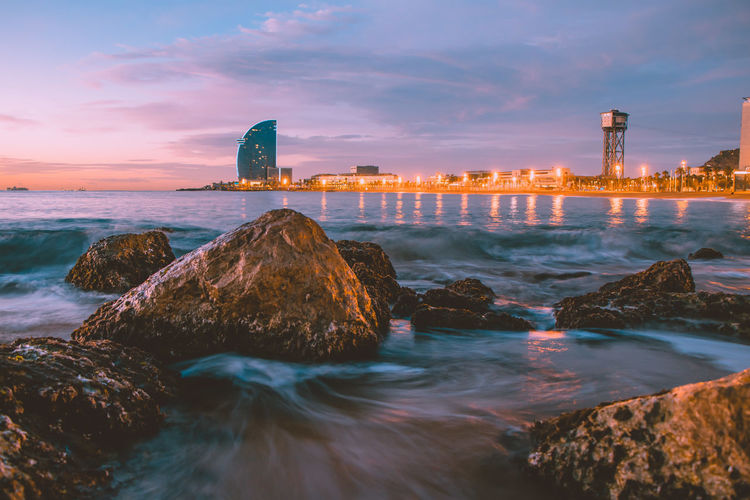 Beautiful view to the beach of Barcelona Barcelona Beach Photography SPAIN Architecture Beach Beachphotography Beauty In Nature Building Exterior Built Structure Cloud - Sky Land Long Exposure Nature No People Outdoors Rock Rock - Object Scenics - Nature Sea Sky Skyscraper Solid Sunrise Sunset Water First Eyeem Photo