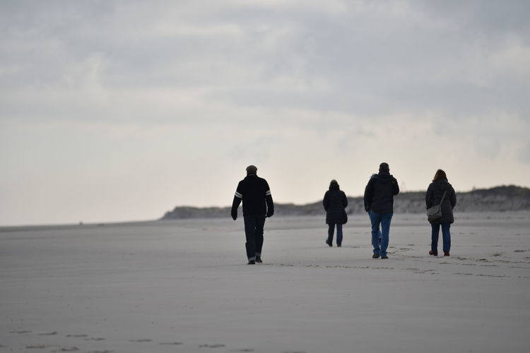 Rear View Of People Waking On Beach Against Sky