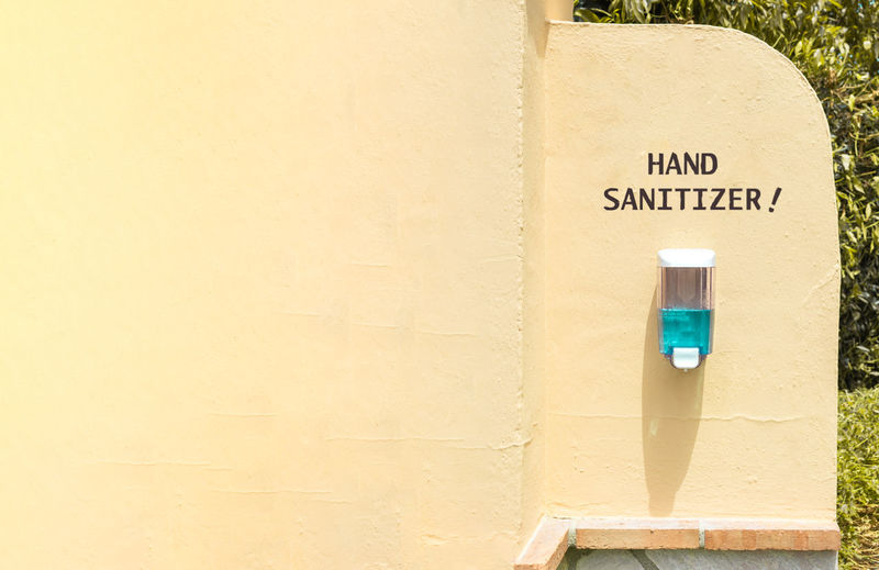 Sanitizer with text on wall