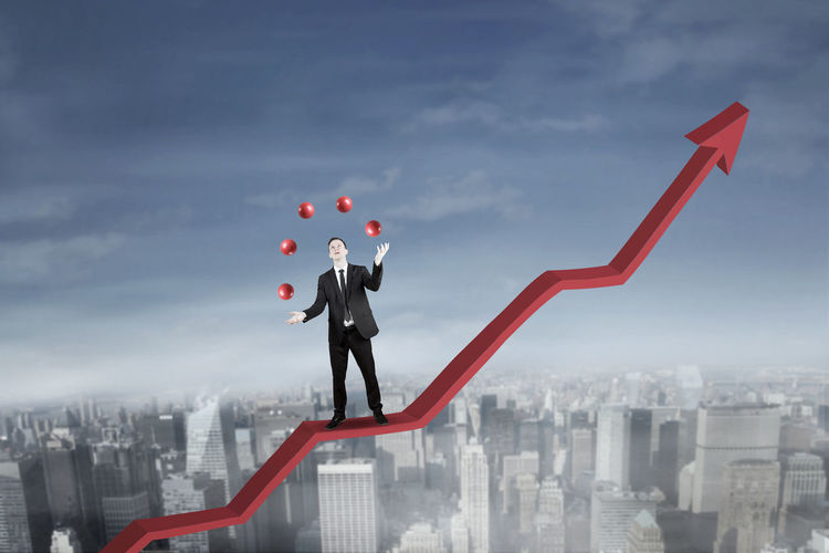 Digital Composite Image Of Businessman Juggling Currency Symbols On Graph Against Cityscape