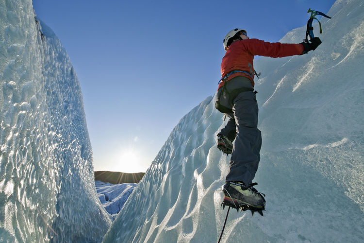 Man on snowcapped mountain against sky during winter