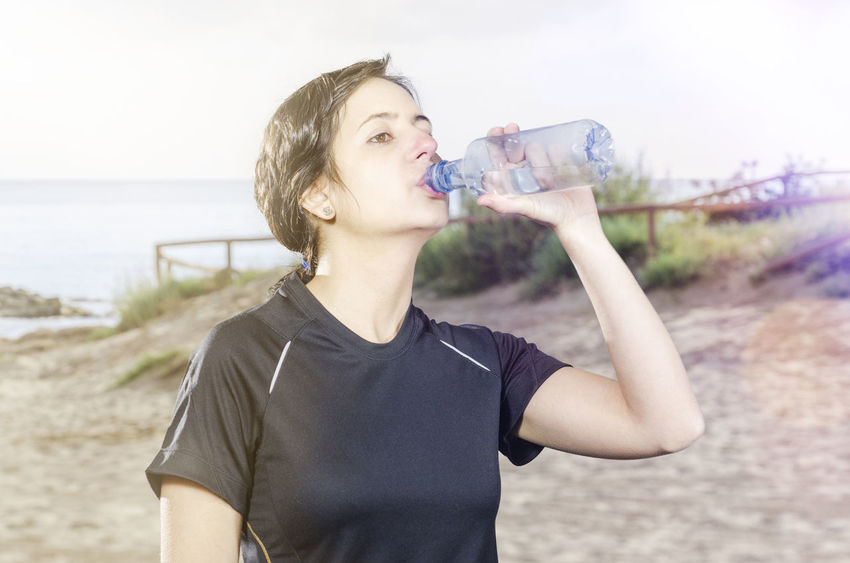 Woman is drinking water in a plastic bottle. Beach Day Drink Drinking Drinking Water Leisure Activity Nature One Person Outdoors Real People Refreshment Running Sand Sea Sky Sport Standing Sunbeam Water Water Bottle  Woman Young Adult