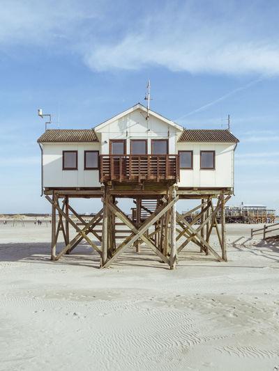Lifeguard hut on beach by sea against sky