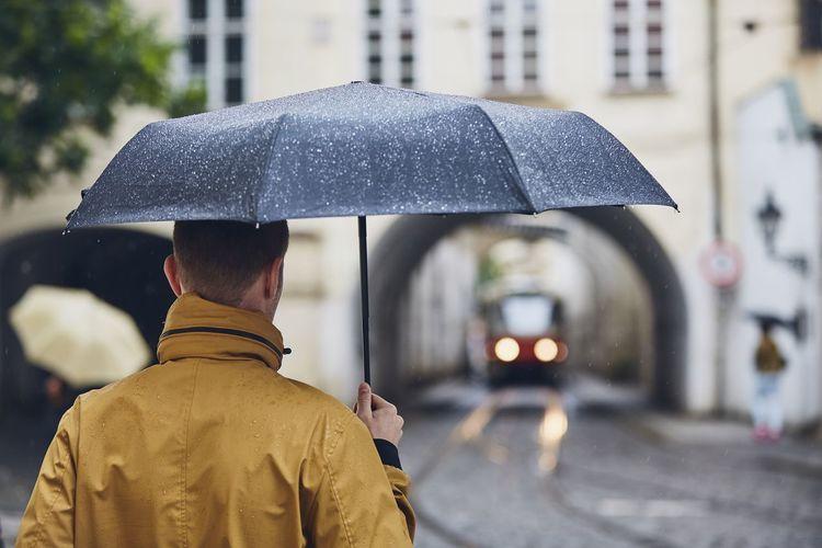 Rear View Of Man Under Umbrella During Rainy Season
