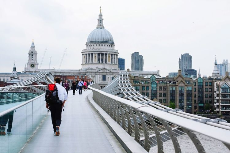 People Walking On London Millennium Footbridge Against St Paul Cathedral