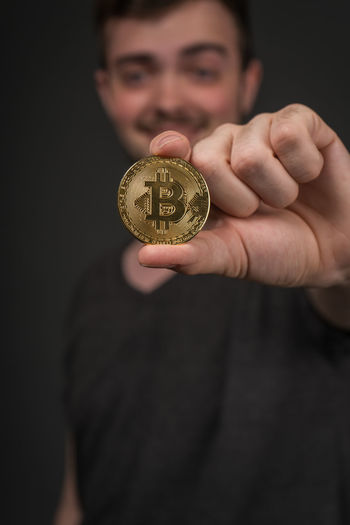 Portrait Of Young Man Holding Bitcoin Against Black Background