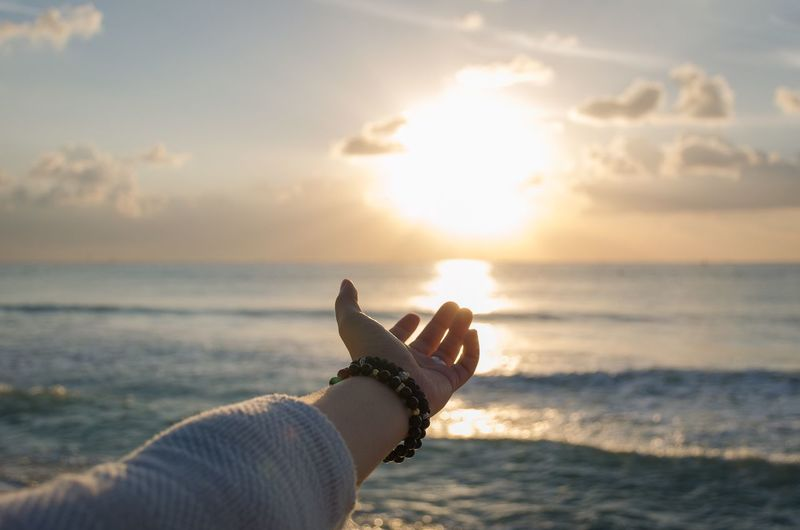 Cropped hand of woman reaching towards sea during sunset