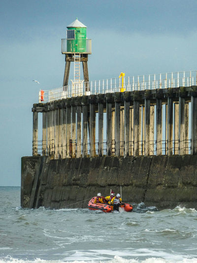 People on lifeboat in sea by pier