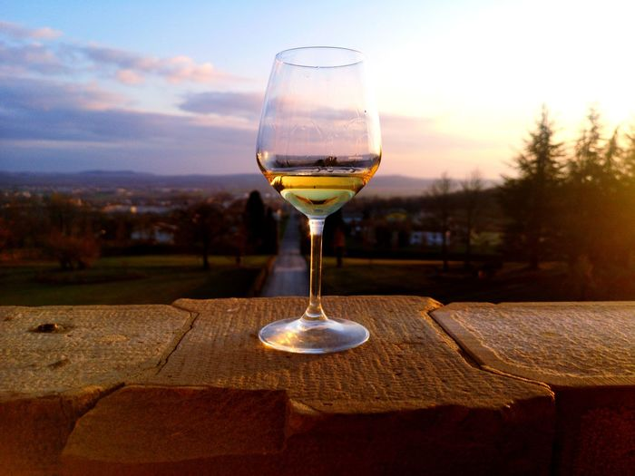 Glass of wine on table against sky during sunset