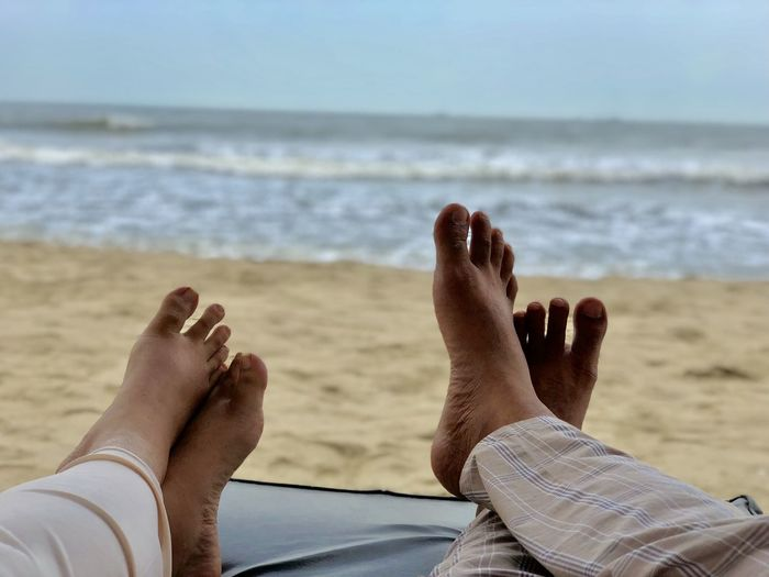Low section of couple relaxing on lounge chair at beach