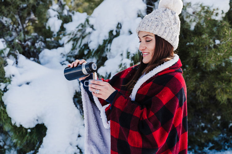 Woman photographing on snow covered landscape during winter