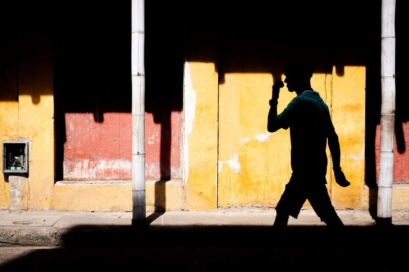 Silhouette man walking on street against colourful building