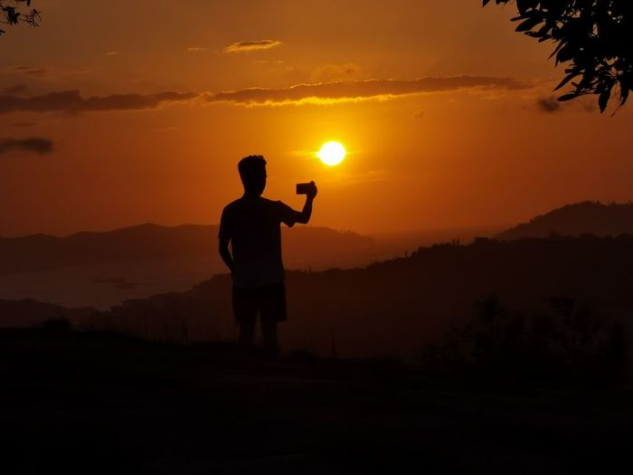 Silhouette man standing on mountain during sunset