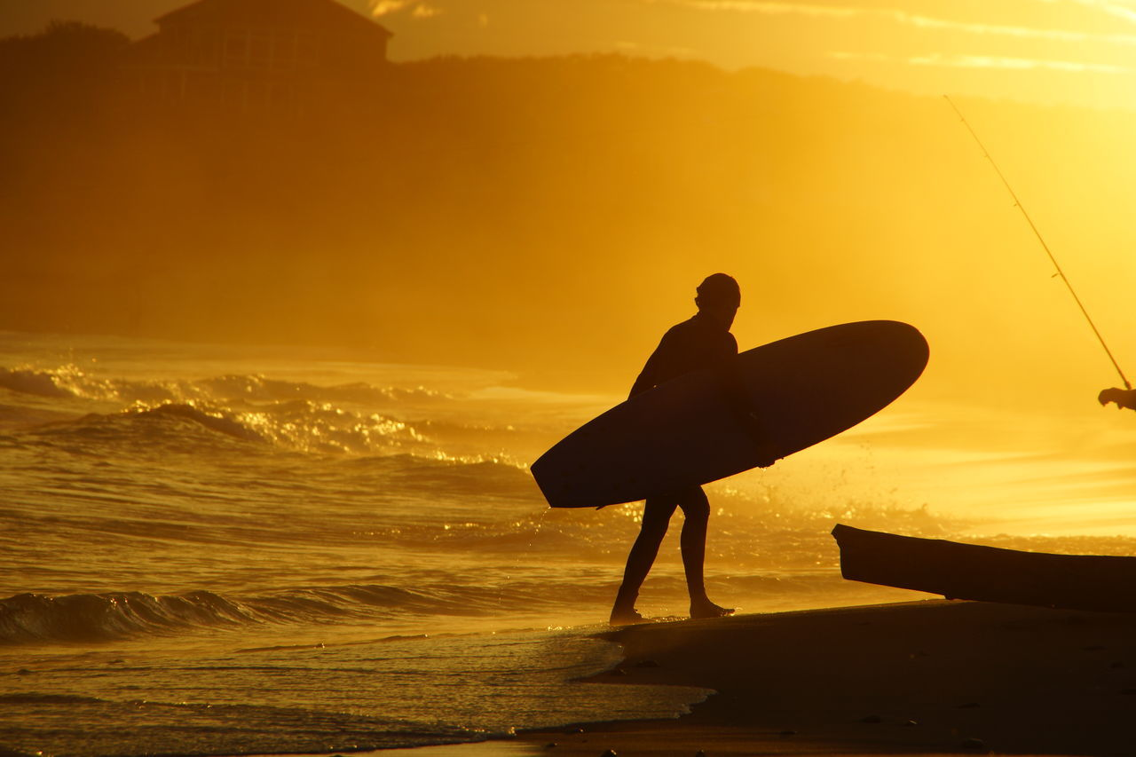 Silhouette man with surfboard at sea shore during sunset
