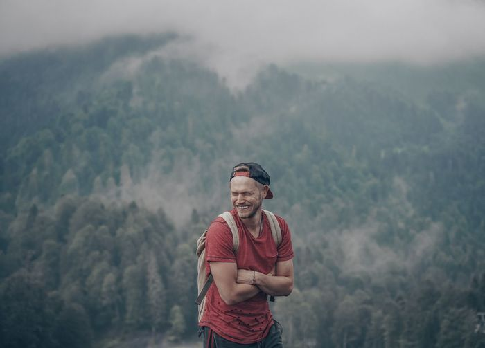 Happy young man standing on mountain