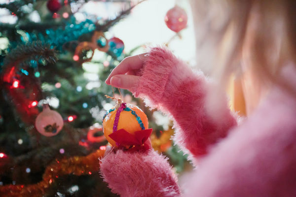 Young girl decorating Christmas tree, holding Christmas ball. Teenage blonde girl wearing pink sweater. Young girl celebrating Christmas at home Celebration Holiday Christmas Tree Decoration christmas tree Close-up Girl Ball Tradition Home Decorate Decorating Fun Holiday Indoors  Event Lifestyles Lights Merry Christmas! Merry Christmas Pine Celebration Female