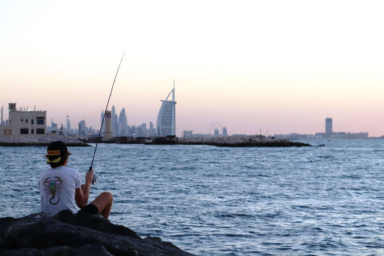 Man fishing in sea against cityscape during sunset