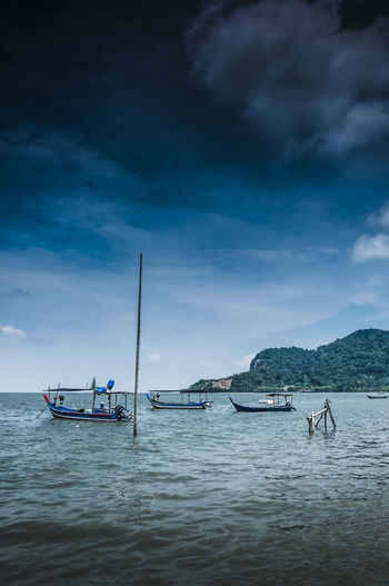 Fishing boats moored in sea against cloudy sky