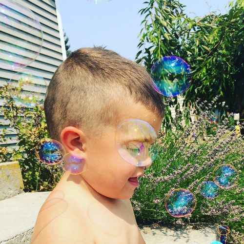 Shirtless boy playing with bubbles at yard during sunny day