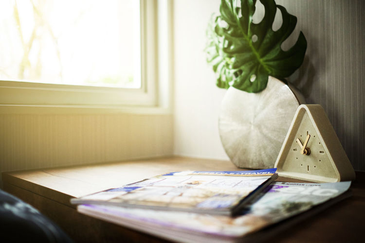 Close-up of magazines and alarm clock on table at home
