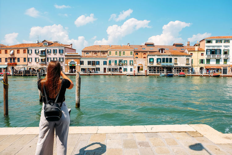 woman taking photo of landscape with buildings Venice Venice, Italy Burano Italy City Cityscape Woman Woman Portrait Woman Power Built Structure Building Exterior Architecture Real People Standing One Person Lifestyles Day Building Casual Clothing Outdoors Rear View Water Sky Nature Cloud - Sky Sunlight Women Hairstyle Canal Taking Photos