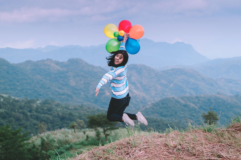 Full Length Of Woman Holding Balloons While Jumping At Mountain Peak Against Sky