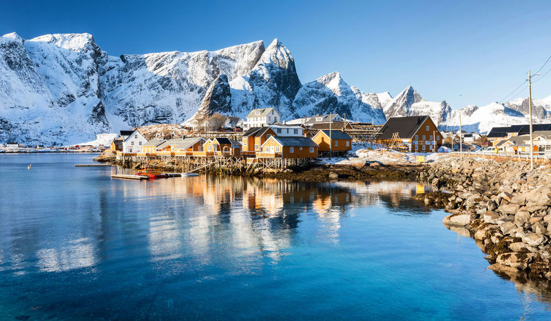 Winter in Sakrisøy Norway Sakrisøy Beauty In Nature Blue Cold Temperature Day House Lofoten Mountain Nature No People Outdoors Reflection Scenics - Nature Snow Snowcapped Mountain Water Waterfront Winter
