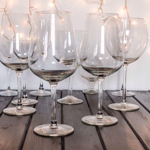 Close-Up Of Wineglasses On Table By Illuminated Lights Against Wall