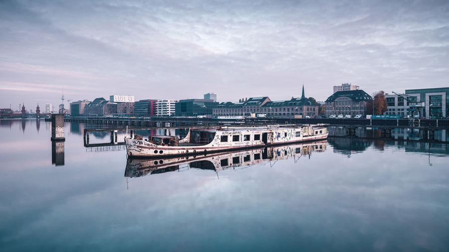 Boat Moored On Lake By Buildings Against Sky
