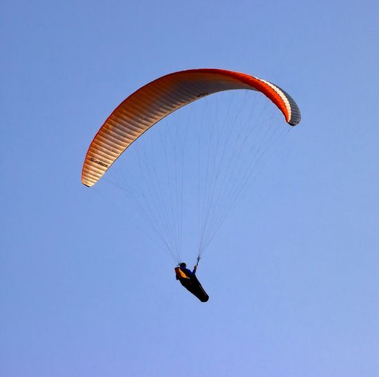 Low angle view of paraglider against clear sky